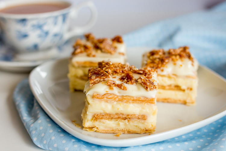 Vanilla Slice with Hazelnut Crunch - creamy layers of custard sandwiched between crisp pastry and topped with frosting and caramelized hazelnuts.   Ideahacks.com