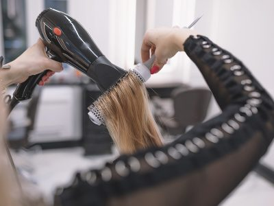 styling a woman's hair using the best round brush for blowouts