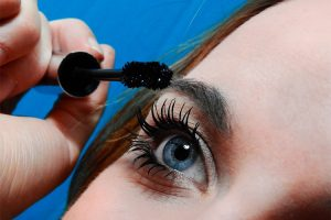 Woman applying black mascara
