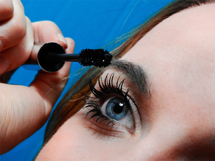 Woman applying black mascara