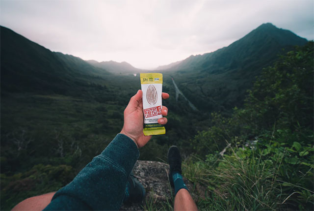 Man at the top of mountain holding a protein bar