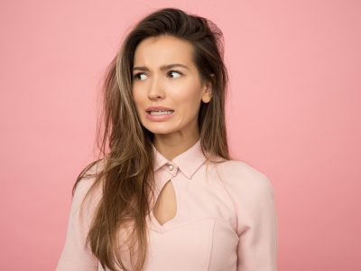 Woman wearing pink dress is doing some facial expression because of her frizzy hair