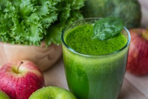 green detox juice in glass and fruits