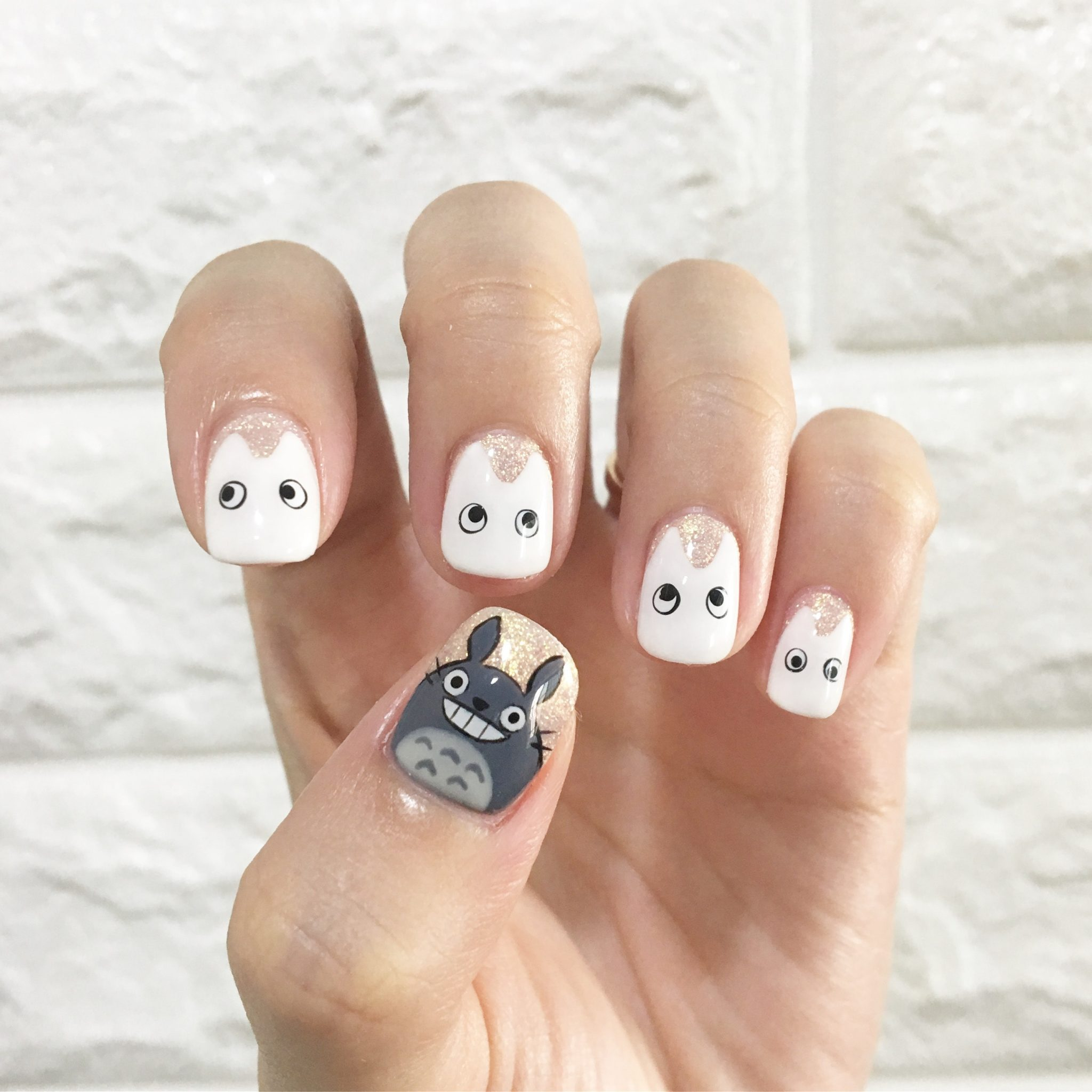 Girl's Fingers painted with the best white nail polish and draw some art on it