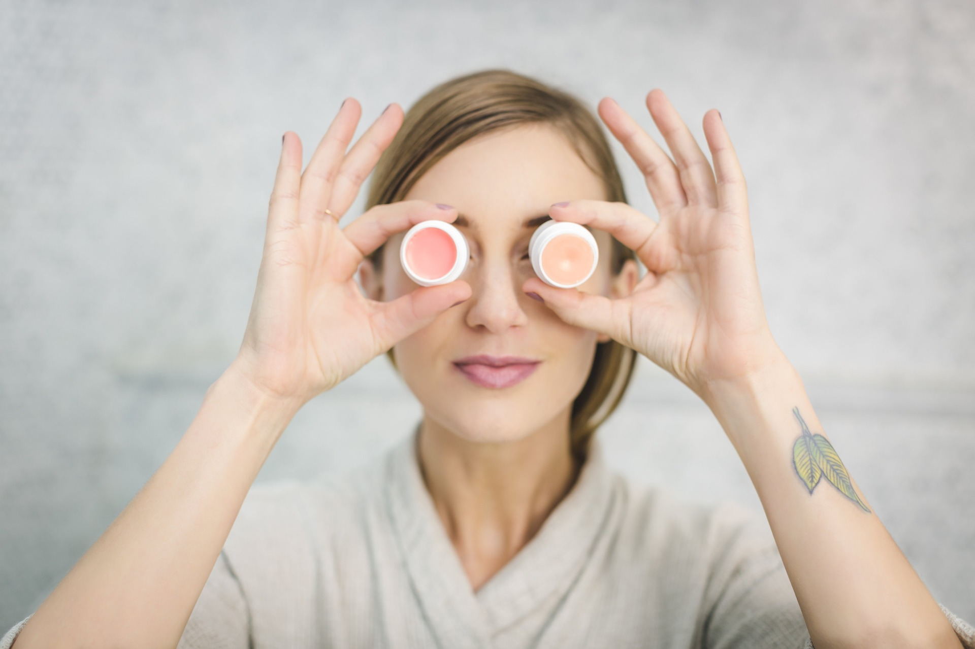 Girl wearing a bathrobe is holding a 2 shades of lip balm and put i on her eyes