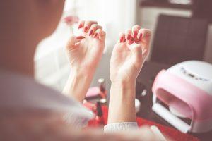 Girl cheeking her fingers after applying the best gel nail polisj