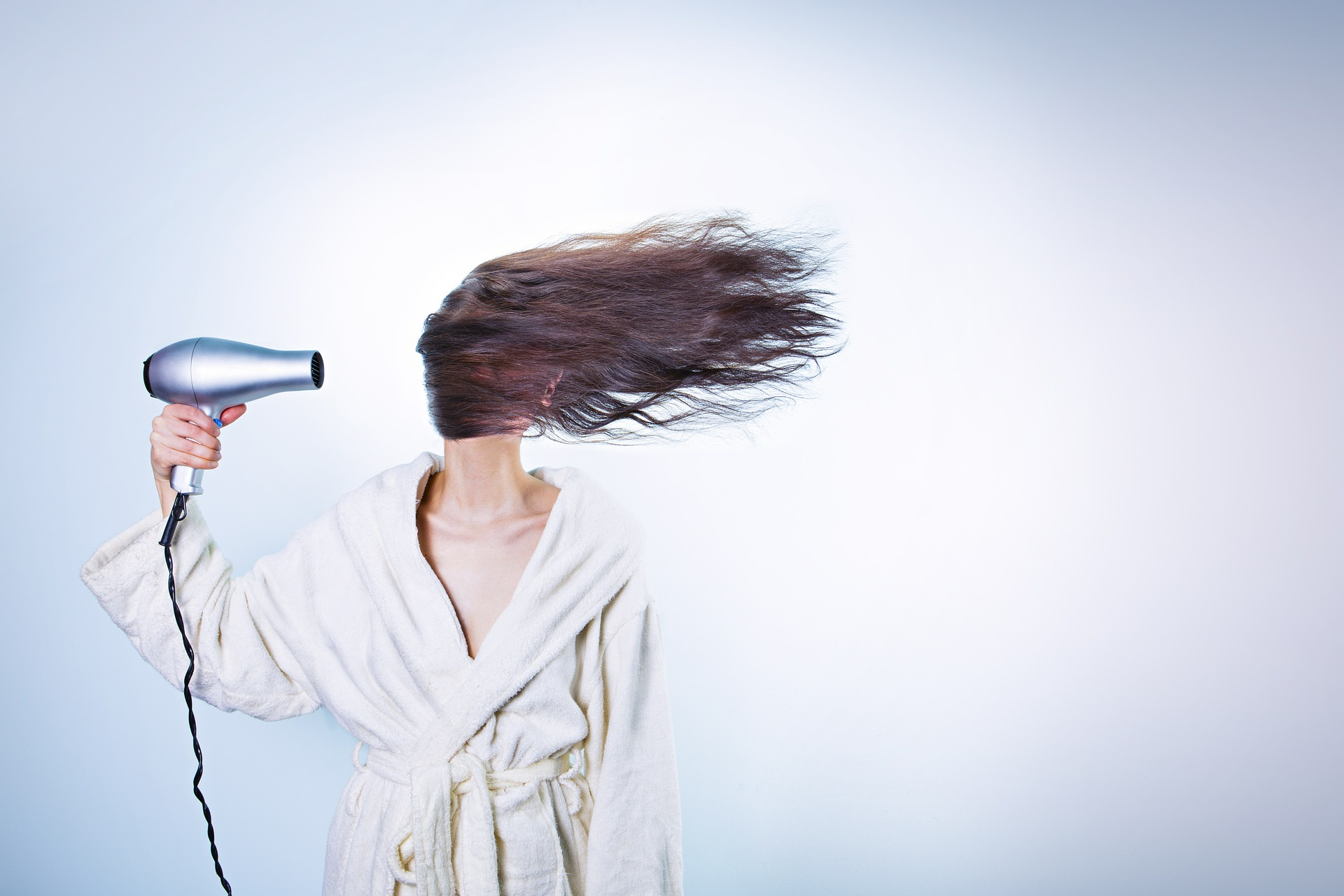 Woman drying her hair using blower