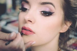 Person applying lipstick on lips of young attractive woman