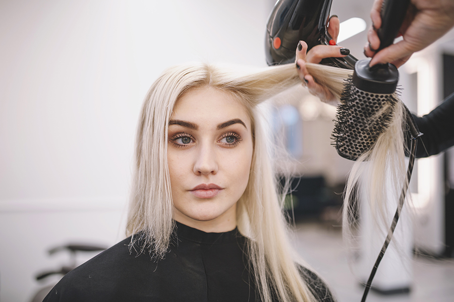 woman styling her hair with the best round brush for blowouts