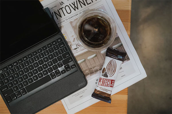 Brown table with protein bar and laptop