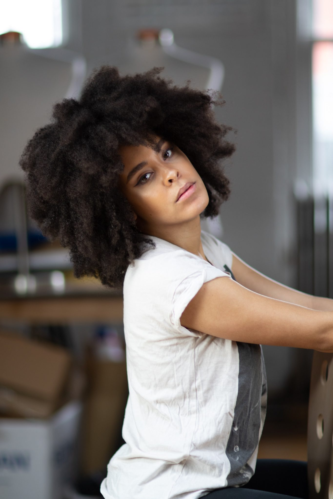 Afro Beautiful Woman wearing a white shirt is showcasing her natural hair