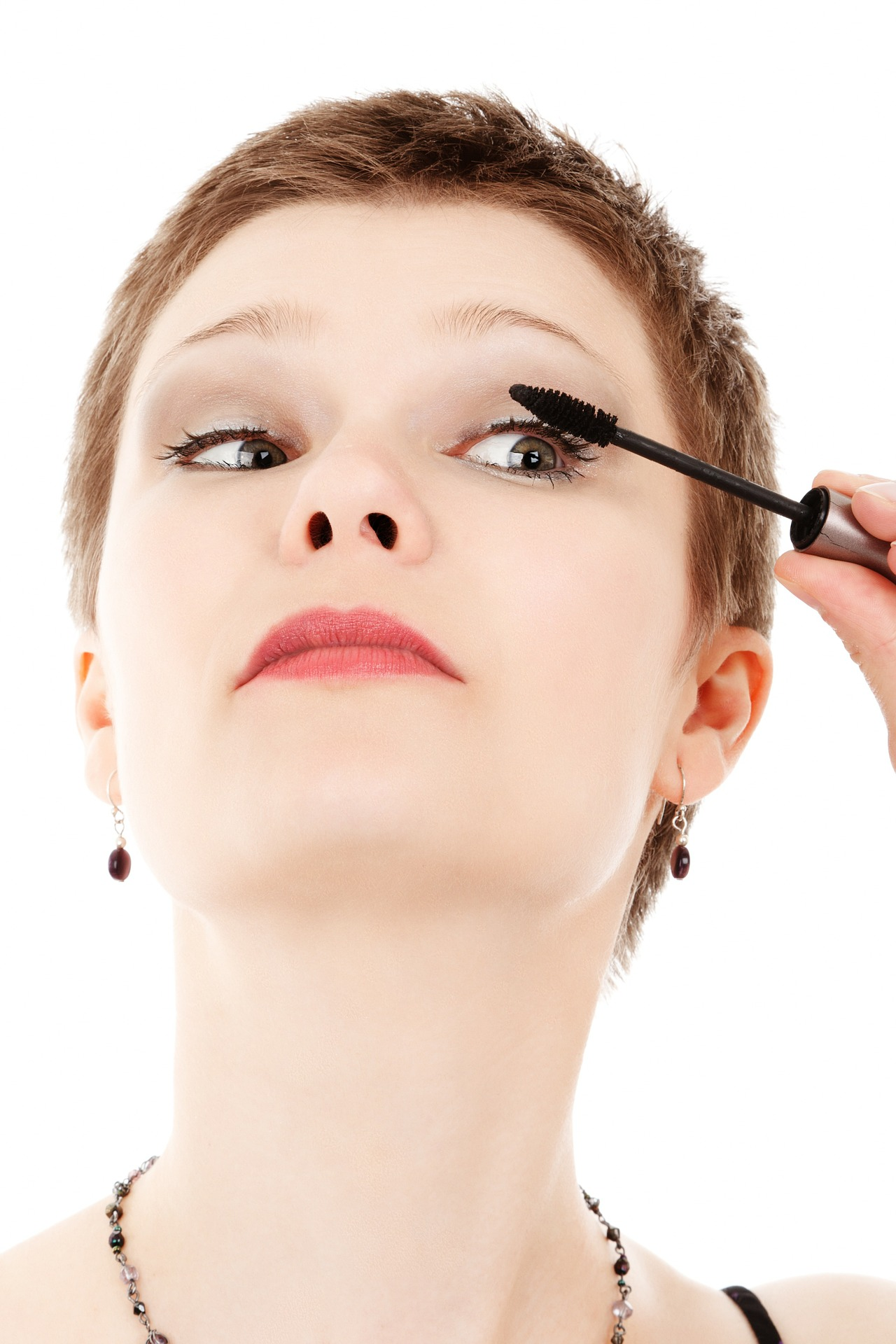 Woman volumizing her eyelash using the mascara she is holding