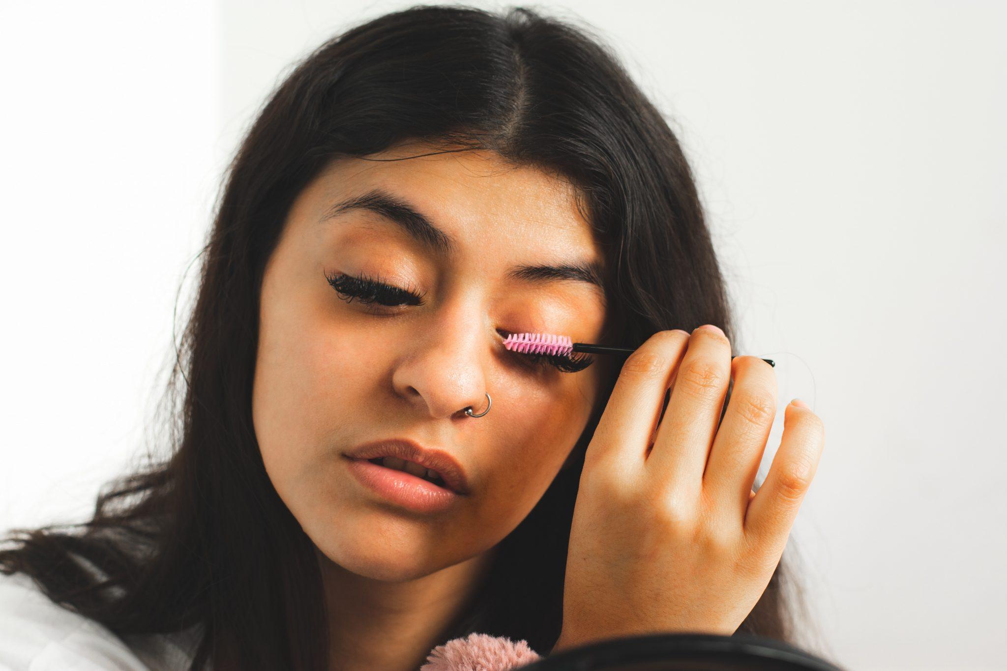 Woman with nose piercing is volumizing her eyelash using the mascara