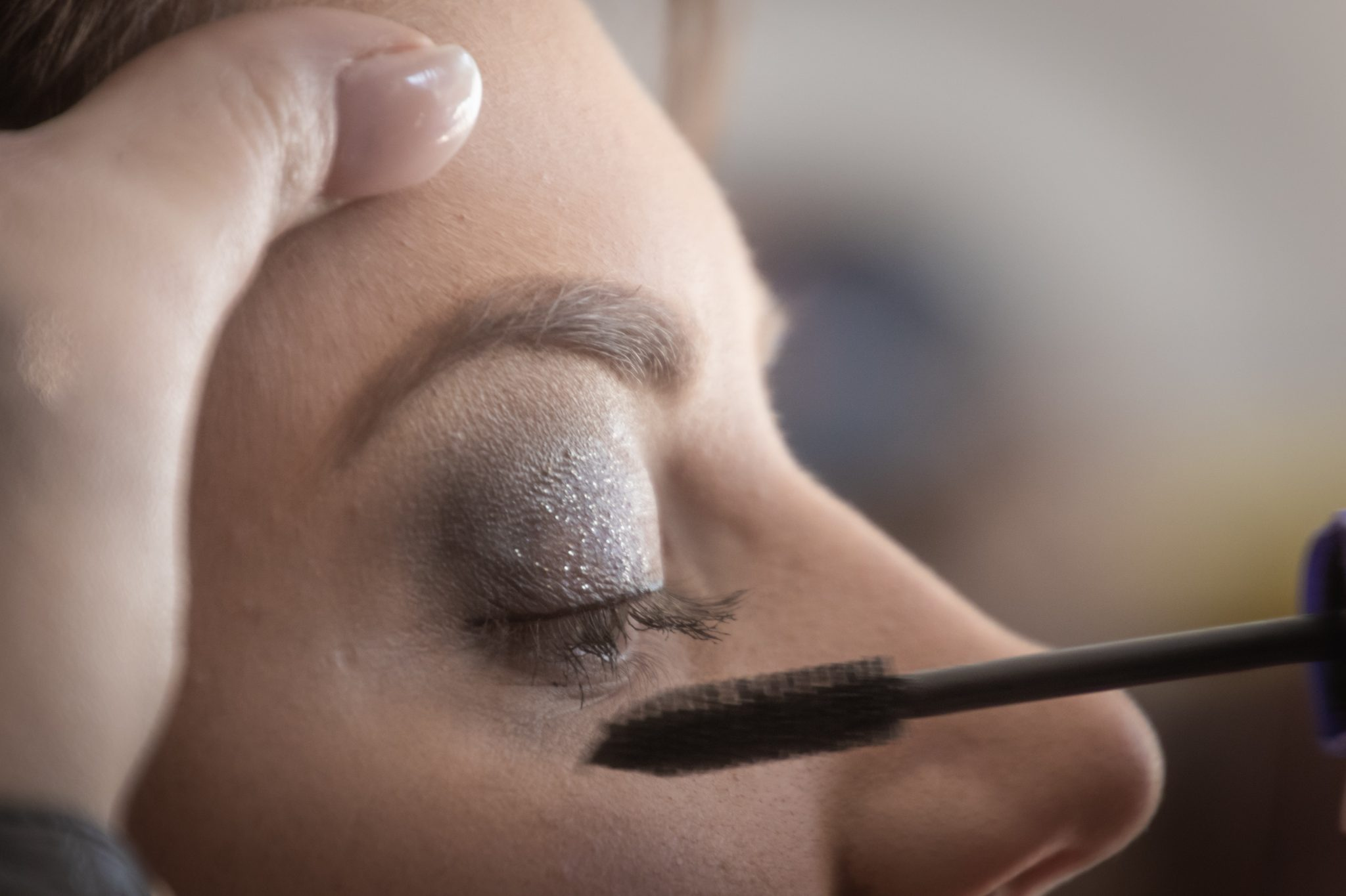 Person is volumizing the eyelash of the woman with violet eye shadow using the  mascara