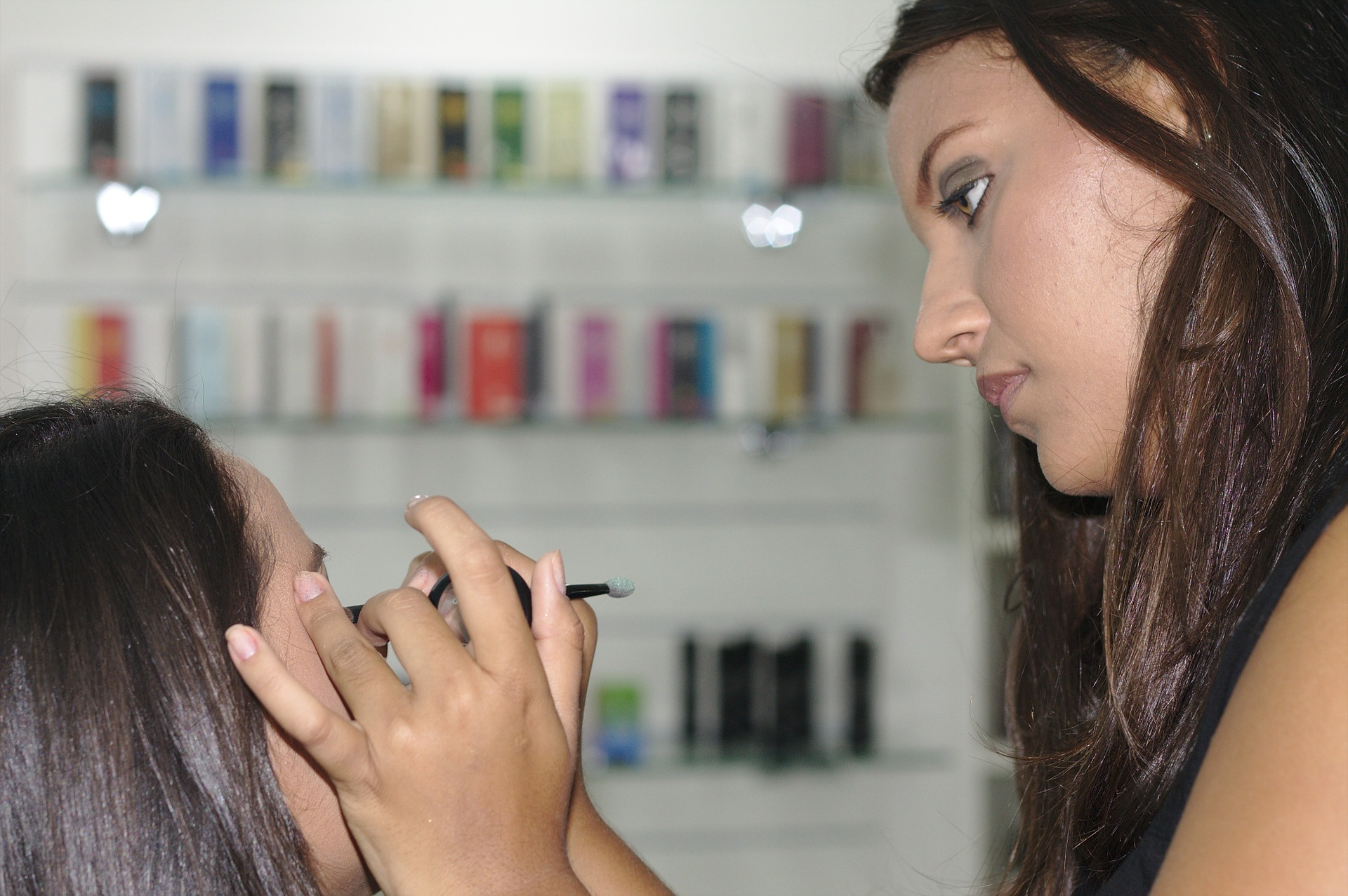 Make up artist is putting a eyeliner to her customer