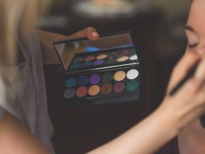 woman applying eyeshadow make up to a girl