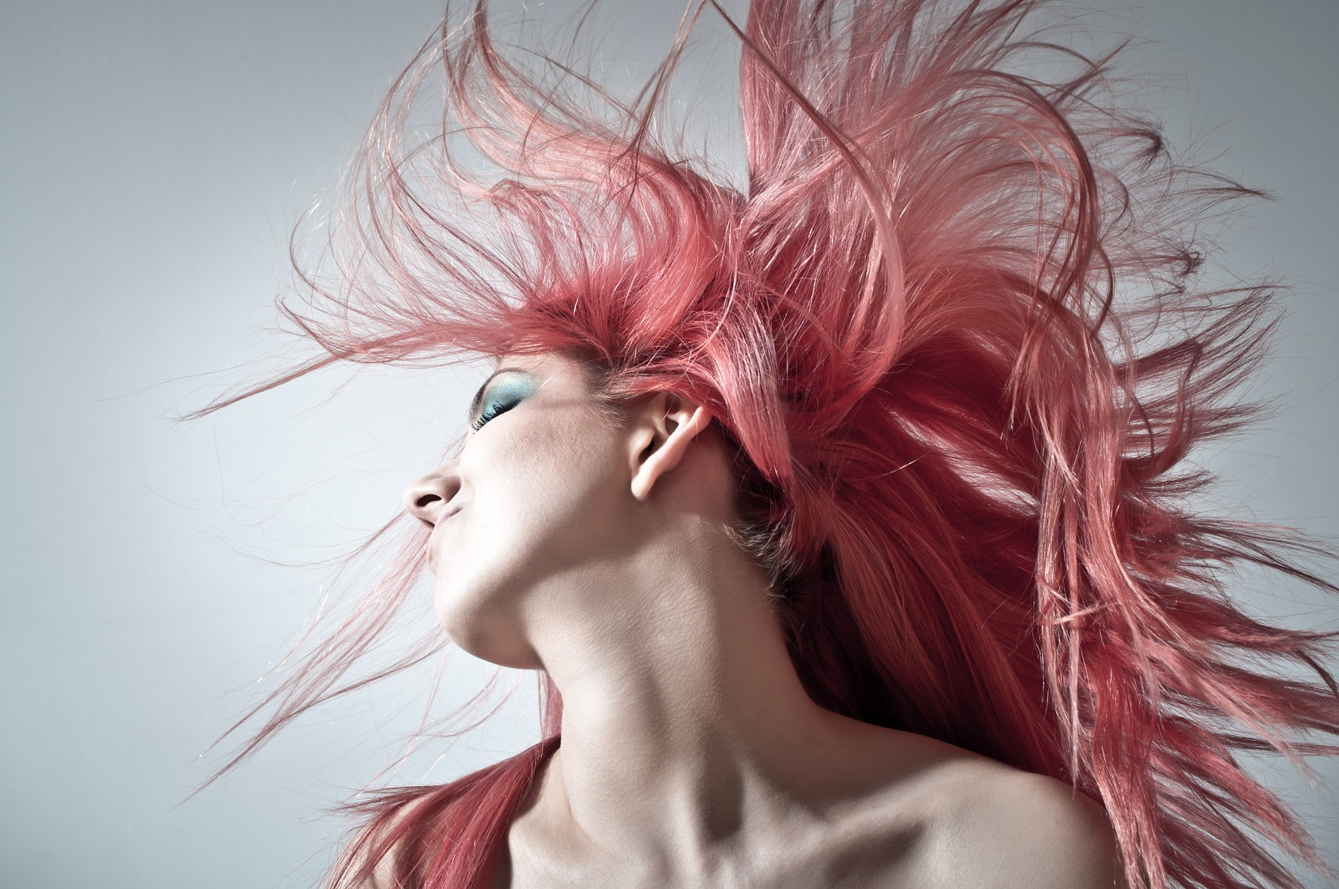 Girl waving her hair has a pink hair color