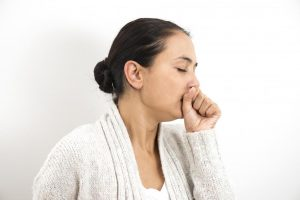 Woman holding her hand over her mouth while coughing