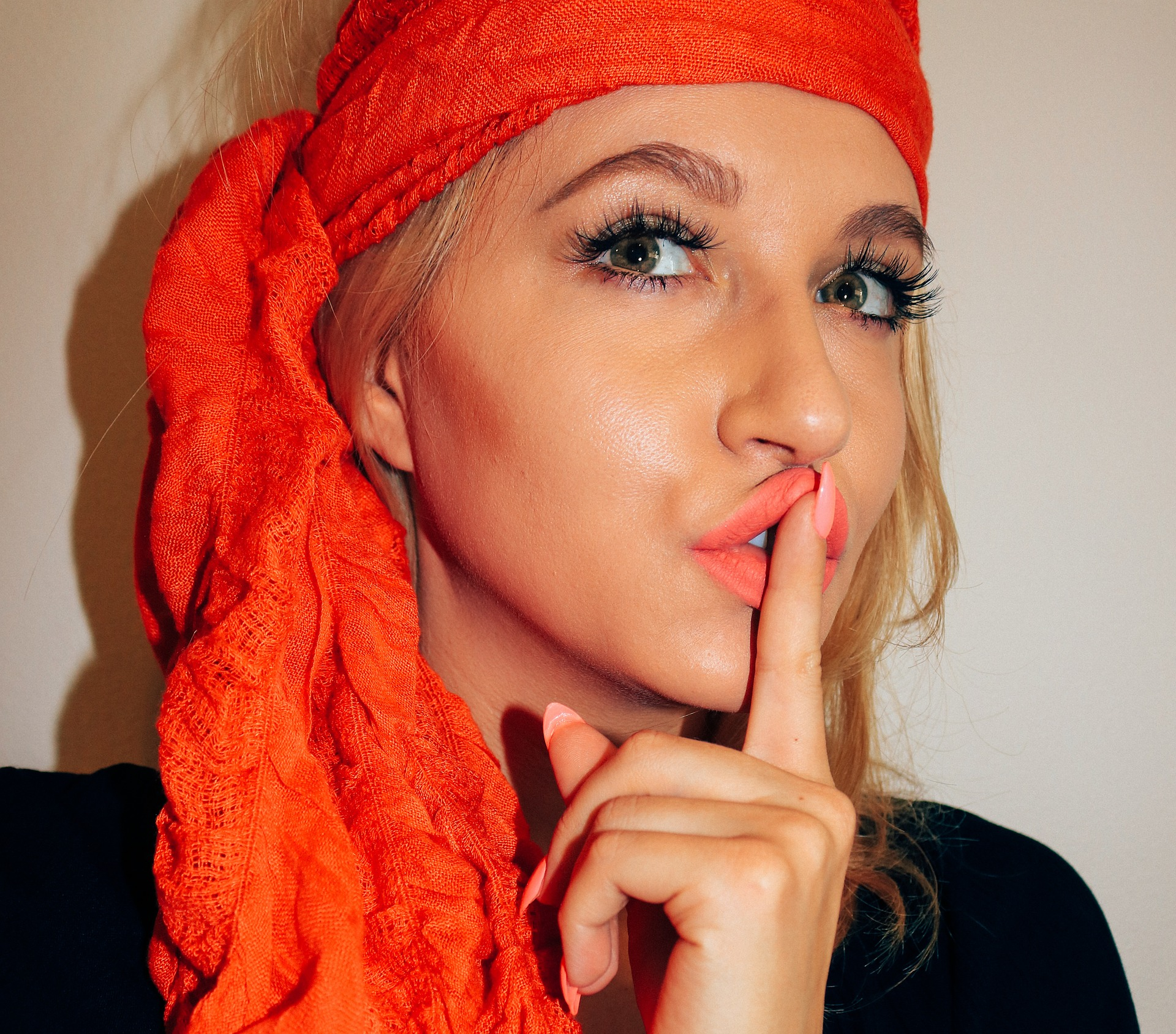 Blonde girl is wearing a read scarf on her head and also she is wearing the best eyelashes