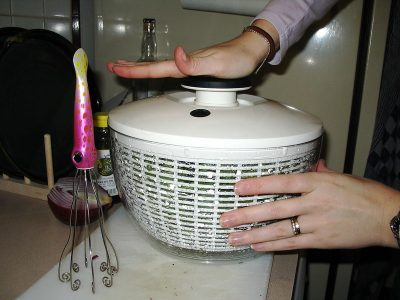a woman using salad spinner