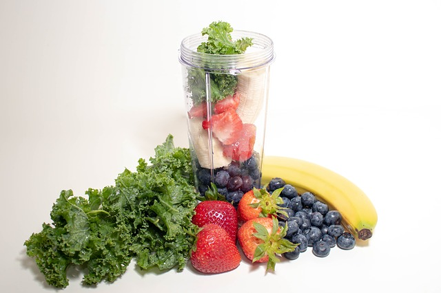 a smoothie maker jar full of fresh veggies and fruits