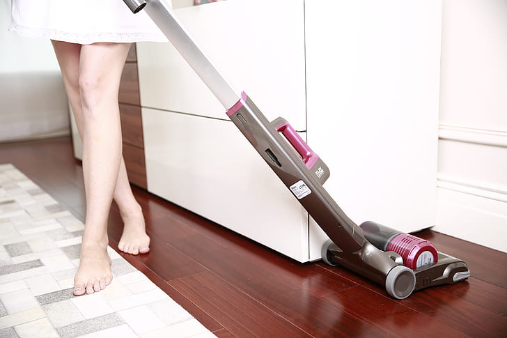 women using vacuum cleaner in the kitchen
