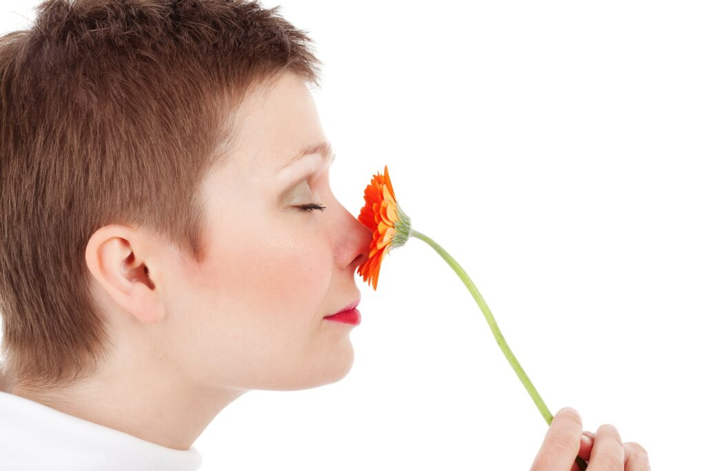 A woman smells a flower as part of olfactory training, which is what some viral tiktok cures are based on