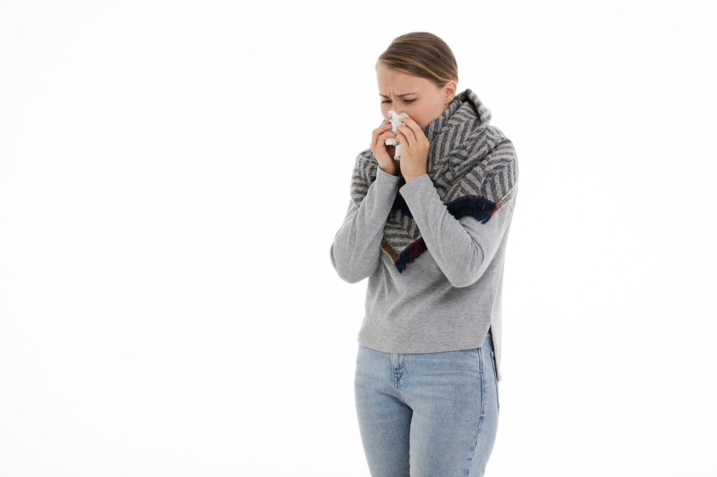 A woman with a stuffy nose holds a tissue to her face
