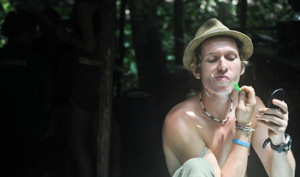 A young man shaving his face outdoors